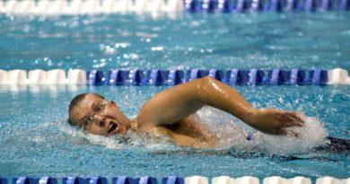 Athlet schwimmt auf Schwimmbahn. Man sieht diesen beim Kraulen.
