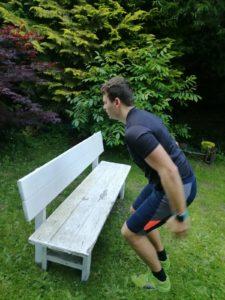 Athlet springt aus der Hocke auf eine Bank (Anfangsphase)
