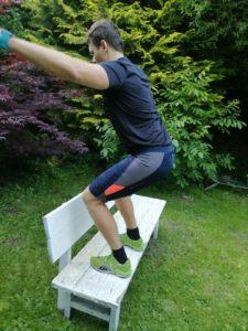 Sportler springt auf eine Bank und führt dabei einen Box Jump aus