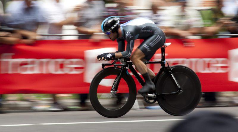 Ein Radfahrer der mit enormen Tempo in aerodynamischer Position sprintet.