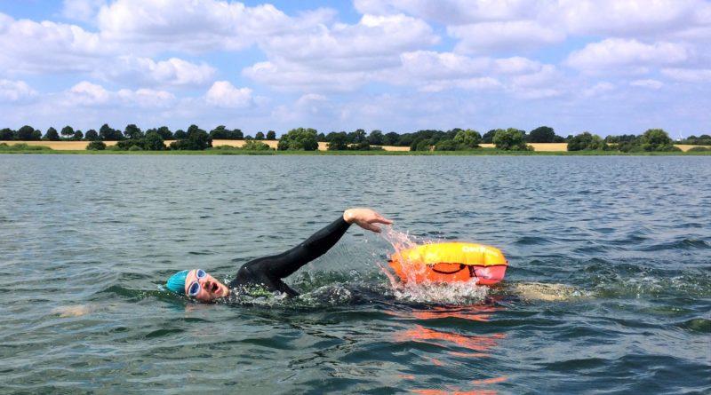 Schwimmer im freien Gewässer mit Schwimmboje beim Kraulen