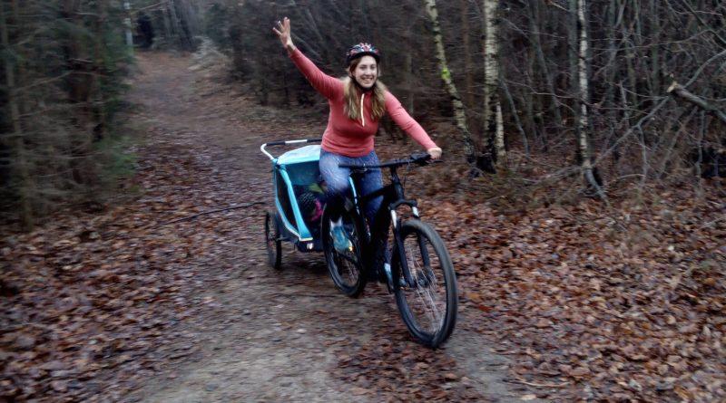 zeigt Sportlerin mit E-bike und Anhänger